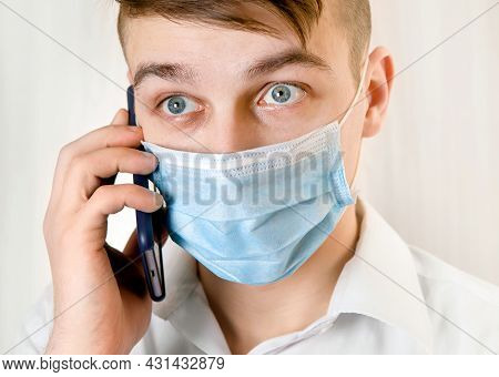 Worried Young Man In Flu Mask Hold A Mobile Phone By The Wall In The Room