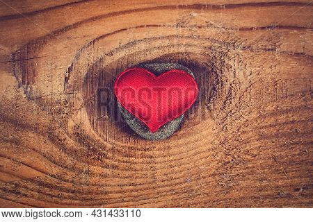 Red Heart Shape On A Pebble And Wooden Planks Background Closeup