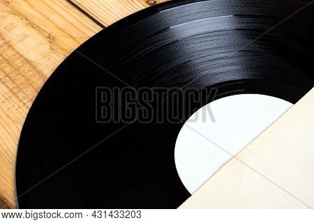 Old Vinyl Record On The Wooden Planks Background Closeup