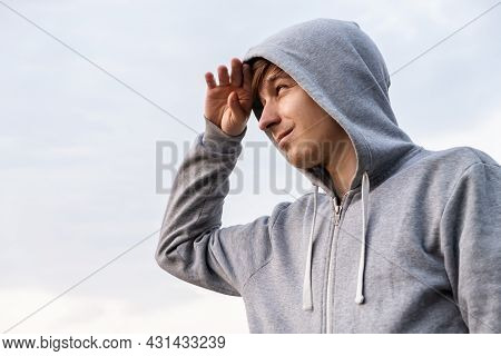 Happy Young Man Portrait In A Hoodie On The Sky Background
