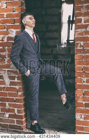Portrait Of Young Man In Classic Suit And Black Patent Leather Shoes Leaning In The Doorway Of Brown