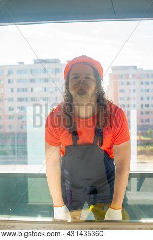 A Sad Engineer In A Helmet Grimaces Behind Glass