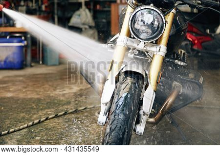 Man Rinsing Motorcycle With Water In Garage To Get Rid Of Dirt Ans Stains