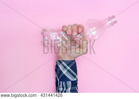 Man Squeezes A Plastic Bottle On A Pink Background. Against The Use Of Plastic. Recycling. Ecology.