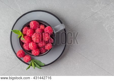 Top View Of Cup With Yummy Fresh Raspberries On Grey Table, Copy Space. Delicious Raw Fruits