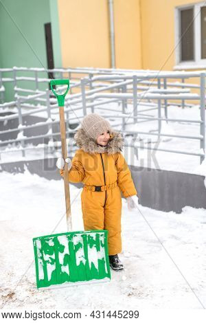 A Girl In An Orange Jumpsuit Is Standing Outside The House On A Frosty Winter Day With A Large Shove