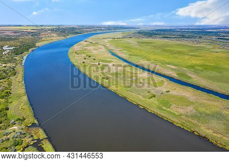 The Blue Of The Sky Is Reflected In The Wide Waters Of The Wide River. Aerial Photography From A Dro