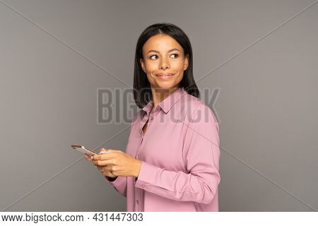 Young Woman With Smartphone In Hand Looking Away To Copy Space. Female In Pink Shirt Typing Text Mes