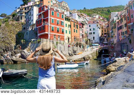 Holidays In Italy. Beautiful Woman Looking The Picturesque Village Overhanging Cliffs Riomaggiore, C