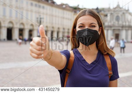 Covid-19 Optimistic Traveler Woman Wearing Black Protective Mask Kn95 Ffp2 Showing Thumbs Up In City