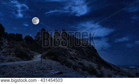 Old Ancient Castle On The Hill At Night. Rocky Peaks Of The Ridge In The Distant Background In Full