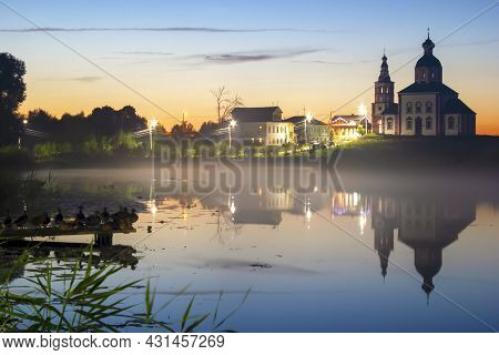 Beautiful Evening Sunset Of A Small Town Reflected In The Lake. Night Fog Over The Lake.