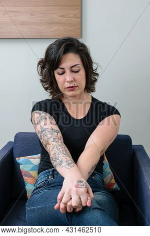 Brazilian Woman, Tattooed, With Her Hands Crossed And Looking Down, Showing Concern And Anxiety.