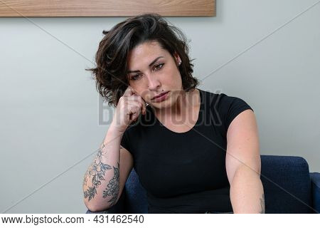 Brazilian Woman, Tattooed, Resting Her Head On Her Hand. Thoughtful And Upset.