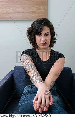 Brazilian Woman, Tattooed, With Her Hands Crossed And Facing The Camera, Showing Her Anxiety.