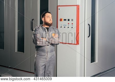 Auto Mechanic Worker Operating Painting Camera In A Car Repair Station Pushing Buttons
