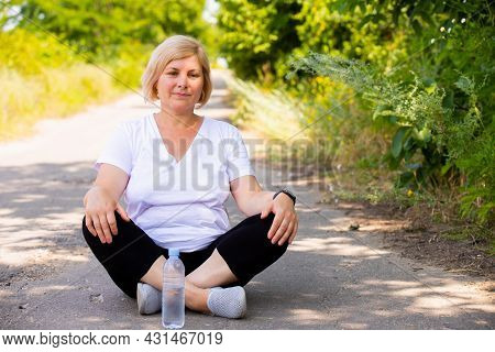 Pensive Woman Resting Sitting On The Road With Cross Legs In Sports Clothes Keeping Her Hands On Her
