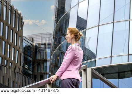 Young Blonde With Tailored Hairstyle In Pink Jacket Stands On Steps And Looks Out At Modern Office B
