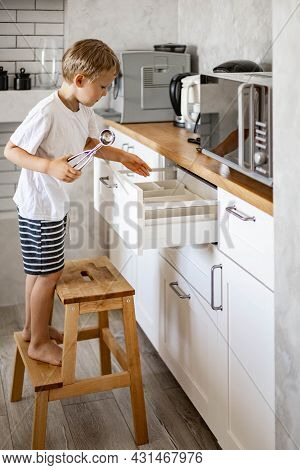 The Boy Helps His Mother In The Kitchen To Put Things In Order. Places Forks, Spoons And Cutlery In