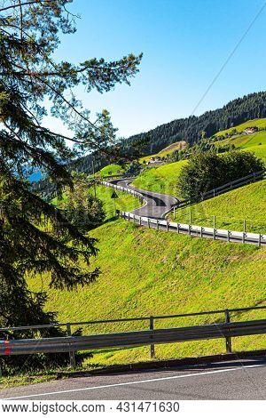 Magnificent Dolomites on a sunny autumn day. Europe, Val de Funes. Tyrol, Italy. Green pastures and mountain roads are fenced with neat wooden fences