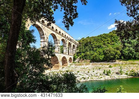 The Pont du Gard is the tallest Roman aqueduct. The aqueduct is a three-tiered arcade of yellow-pinkish limestone. Masterpiece of ancient Roman architecture on the shallow Gardon River.