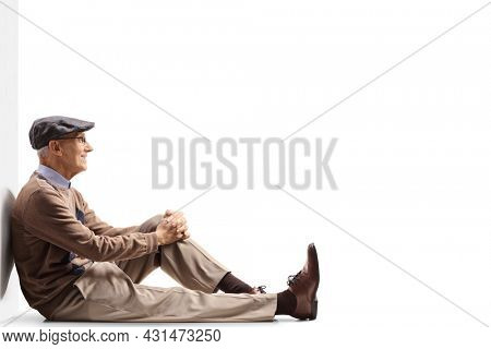 Elderly man sitting on the gorund and leaning on a wall isolated on white background