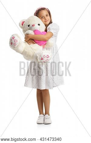Full length portrait of a girl in a white dress hugging a big teddy bear isolated on white background