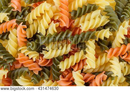 Background Of Raw Tricolor Fusilli Gluten Free Pasta With Spinach And Tomato. Italian Colorful Macar