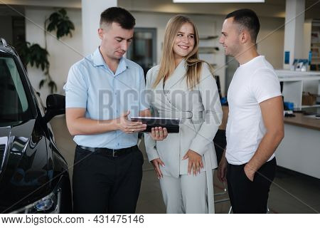 Salesperson Talking With Couple And Help Choosing New Car. Man And Woman In Car Showroom. Man Using