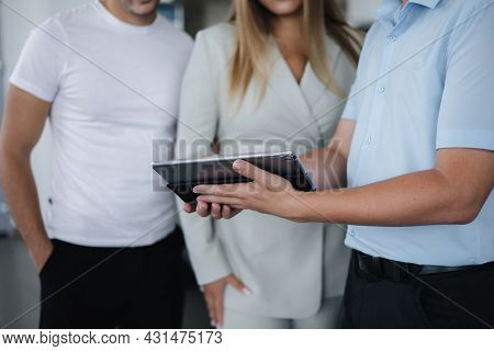 Middle Selection Of Salesperson Talking With Couple And Help Choosing New Car. Man And Woman In Car