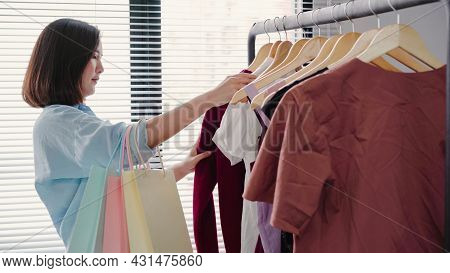 Asian Woman Shopping Clothes. Shopper Looking At Clothing On The Rail Indoors In Clothing Store. Bea
