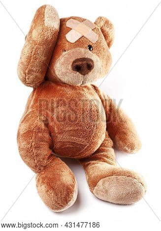 Teddy bear with bandage on the forehead isolated on white background. Child role modeling of doctor.