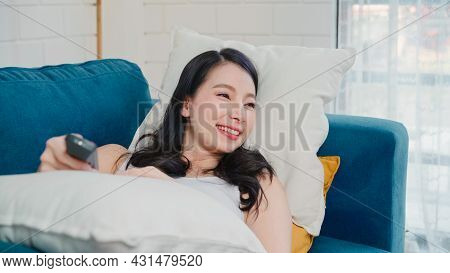 Young Asian Woman Watching Tv At Home, Female Feeling Happy Lying On Sofa In Living Room. Lifestyle