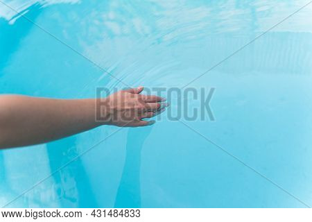 A Young Woman Sliding Over The Water In The Pool. Rest In The Hotel Pool, Summer