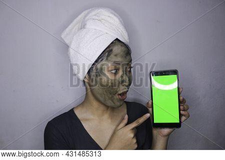 Shock Asian Woman Showing Blank Screen When She Use Beauty Face Mask