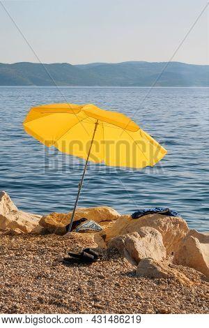 Yellow Beach Umbrella On Summer Coast. Sea Beach With Sun Umbrella Is Waiting For Tourists On Sunset