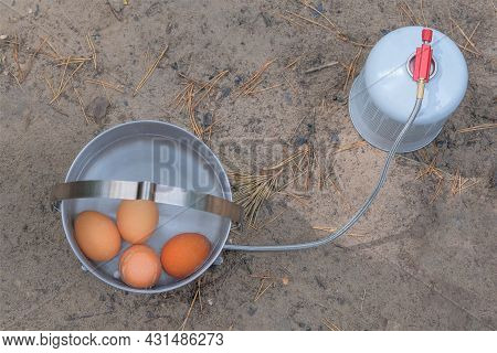 Traveler Foods For Outdoor Activities. Eggs In Pot In The Green Forest. Camping Food Making.