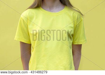 Mockup Of Yellow Cotton T-shirt. Teenage Girl In Yellow T-shirt On Yellow Background. T-shirt Mockup