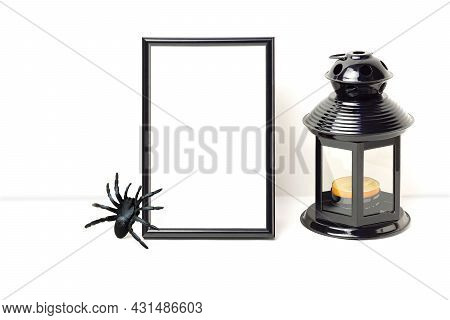 Mockup Photo Frame With Spider And Black Lantern With Candle. Empty Photo Frame Mockup For Showcasin