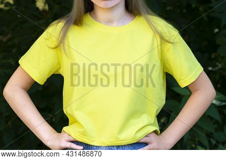 Mockup Of Yellow Cotton T-shirt. Teenage Girl In Yellow T-shirt On Background Of Green Foliage. T-sh