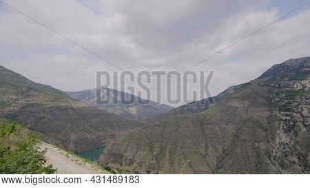 Beautiful River In Rocky Mountains On Background Of Cloudy Sky. Action. Turquoise River Among Rocky