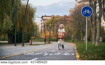Young Woman With Curly Hair In Hat And Stylish Dressed Riding Bicycle On Bike Lane In Urban Park Or