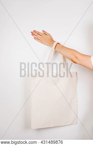 Female Hand Holding Eco-bag. Mocap Of Reusable Cotton Eco-bag On White Insulated Background For Text