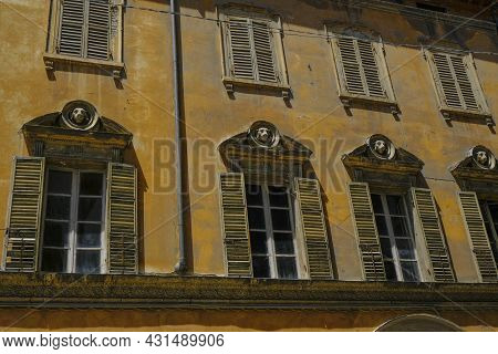 Facade Of The Baroque Yellow Building With Windows And Shutters And Decorative Elements Made As Dogs