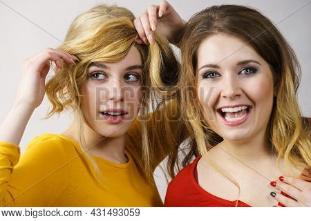 Woman Playing With Her Female Friend Long Ombre Color Hair. Different Hairdo Colors, Haircare And Ha