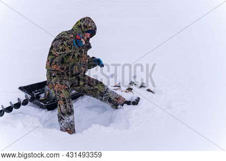 Fisherman Fishing On A Winter Lake Against A Background Of Forest Sky. Winter Fishing