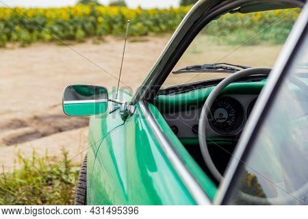 Classic Car Chrome Mirror. Volksvagen Karmann Ghia Coupe, Green Retro Car On Sunflower Field. Italia