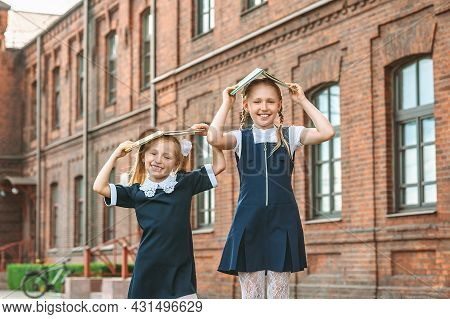 Two Cheerful Schoolgirls Are Holding Books Over Their Heads. First Day Of School. Concept On The Top