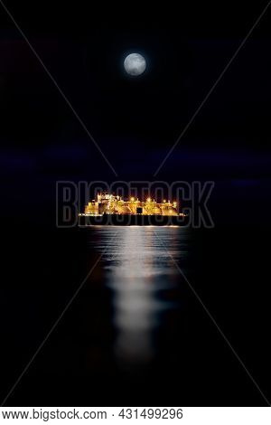 Gas Carrier At Night Against The Background Of Dark Sea. Tanker With Liquefied Gas In The Moonlight.