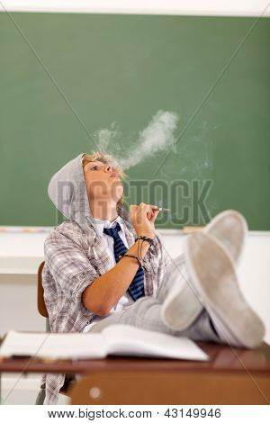 troublesome teen boy smoking in classroom